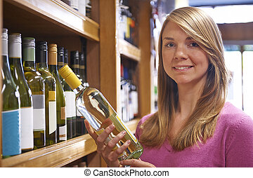 Woman Choosing Bottle Of White Wine In Supermarket