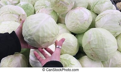 Woman choosing cabbage at the market. Raw food, veggie concept.