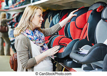 woman choosing child car seat for newborn baby in shop ...