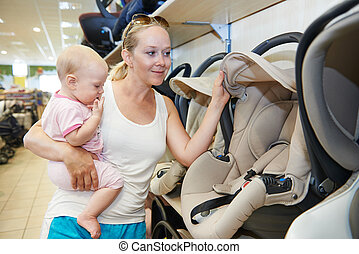woman choosing child car seat with little baby in shop ...