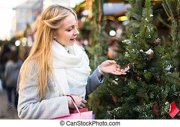 Woman choosing Christmas tree