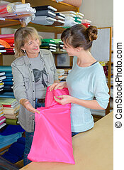 woman choosing cloth fabrics in store