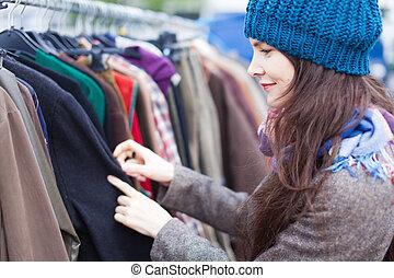 Woman choosing clothes at flea market. - Attractive woman...