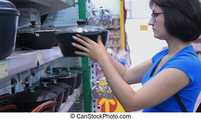 Woman choosing cooking pot in the store - Young woman...