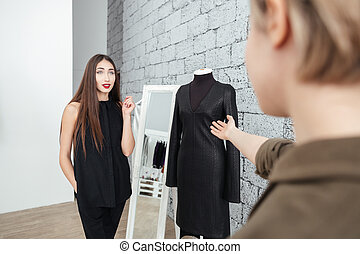 Woman choosing dress in clothing store