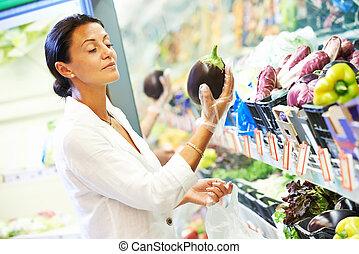 woman choosing eggplant. Vegetable shopping in supermarket