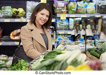 woman choosing fruits and vegetables at supermarket
