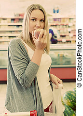 Woman choosing fruits in grocery store.
