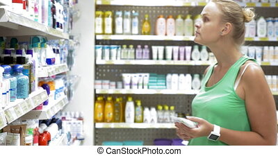 Woman choosing goods in beauty care section of store