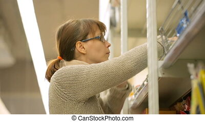 Woman choosing goods in supermarket