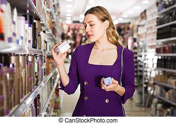Woman choosing hair care cosmetics in store