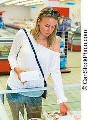 Woman choosing ice-cream in the supermarket.