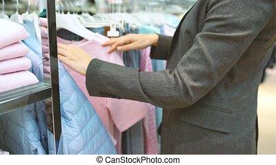 Woman choosing items during shopping at clothing shop -...