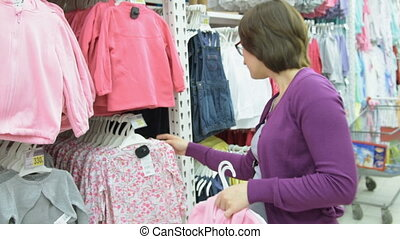 Woman choosing kids clothing in the hypermarket - Young...