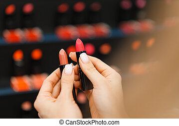 Woman choosing lipstick in cosmetics store