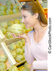 woman choosing melons