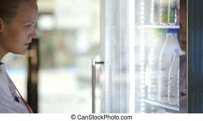 Woman choosing milk at the shop