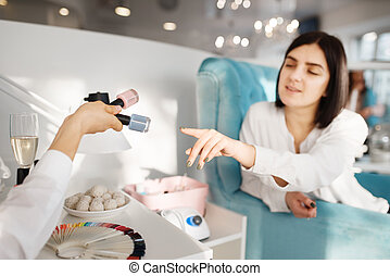 Woman choosing nail varnish in beauty salon