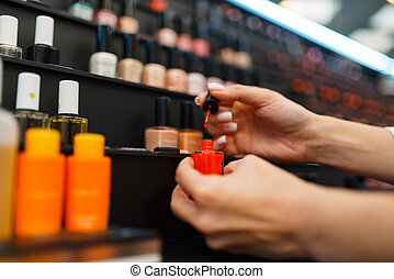 Woman choosing nail varnish in cosmetics store