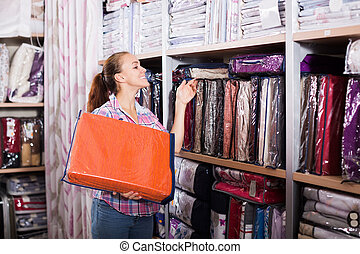 Woman choosing new bed linen - Happy adult woman choosing ...
