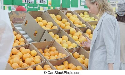 Woman choosing orange at fruit vegetable supermarket