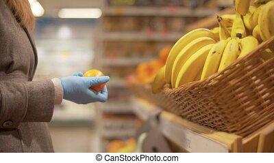 Woman choosing oranges in the supermarket