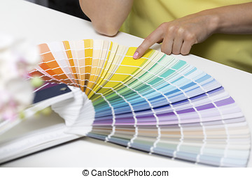 woman choosing paint color from tone samples