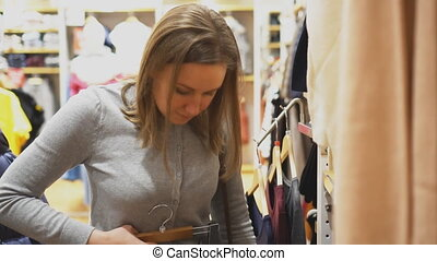Woman choosing pants in clothing store.