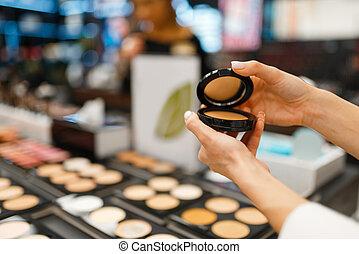Woman choosing powder in cosmetics store