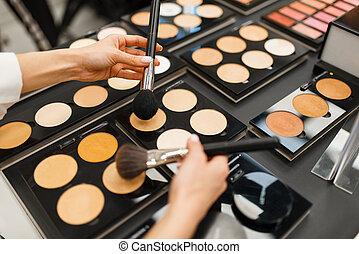 Woman choosing powder tone in cosmetics store