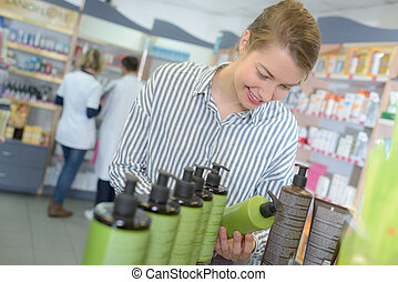 Woman choosing product in chemists shop
