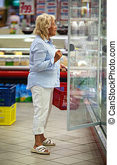 Woman choosing products in open fridge with dairy