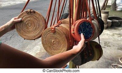 Woman choosing rattan eco bags in the art shop on Bali...
