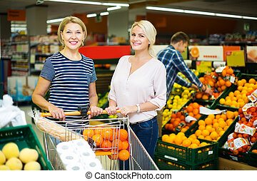 Woman choosing seasonal fruits