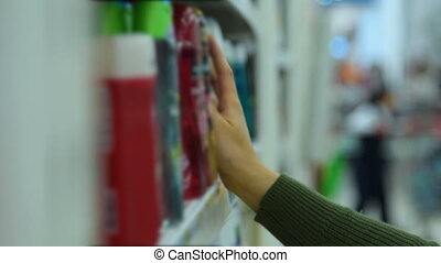 Woman choosing shampoo in the store - Woman choosing a...