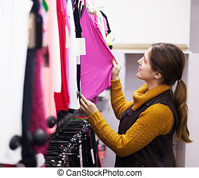 woman choosing shirt at clothing store