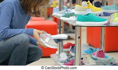 Woman choosing shoes at shoe store