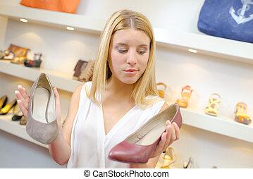 Woman choosing shoes in a shop