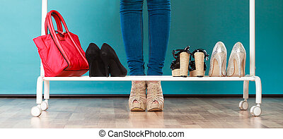 Woman choosing shoes to wear in mall or wardrobe - Closeup...