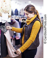 woman choosing skirt at  store