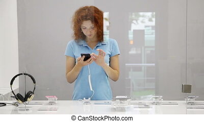 Woman choosing smartphone in store - Young ginger woman in a...