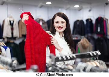 woman choosing sweater at clothing store