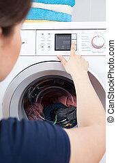 Woman choosing the washing program on a washing machine
