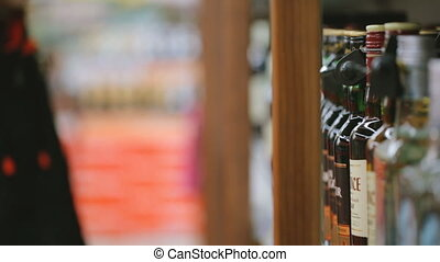 Woman choosing wine at liquor store