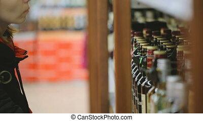 Woman choosing wine at liquor store