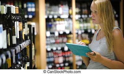 Woman choosing wine using pad