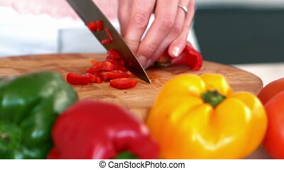 Woman chopping a red pepper
