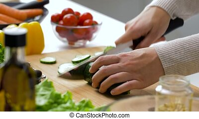 woman chopping cucumber with kitchen knife at home - healthy...