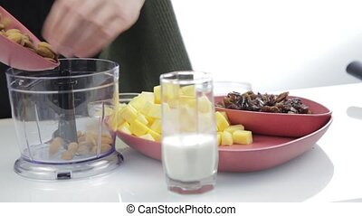 woman chopping nuts in a blender for cooking healthy food