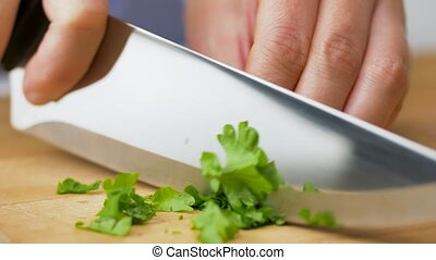 woman chopping parsley with kitchen knife at home - healthy ...